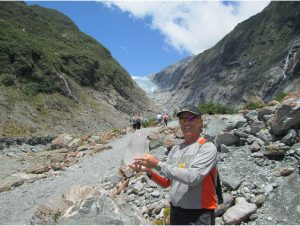 Rocky holding ice from Franz Josef Glacier in the background.