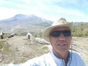 Rocky-selfie looking south at the missing face of Mt. St. Helens, with the many miles of devastation still visible some 35 years later.