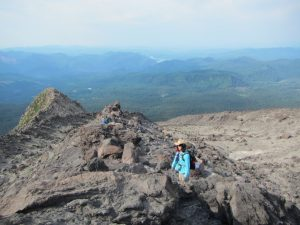 Pam taking a break at ~6600' elevation – still climbing the boulder fields